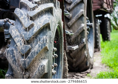 Transportation, technology, agriculture. The wheels of the tractor with mud, close-up. Without the use of filters, enhanced contrast. - stock photo