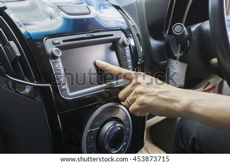Transportation,technology and vehicle concept - man using car system control pushing panel button screen interface modern design   - stock photo