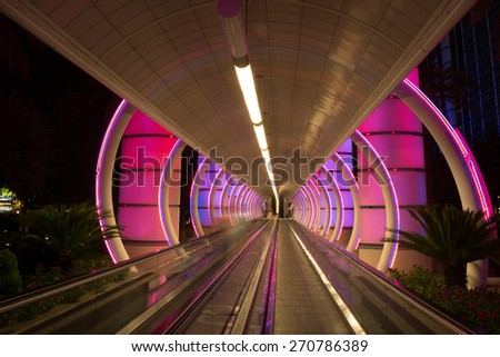 Transportation tunnel with moving sidewalk and color show