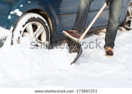 transportation, winter and vehicle concept - closeup of man digging up stuck in snow car - stock photo
