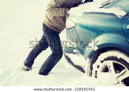 transportation, winter and vehicle concept - closeup of man pushing car stuck in snow - stock photo