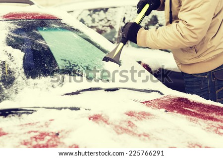transportation, winter and vehicle concept - closeup of man scraping ice from car windshield with brush - stock photo