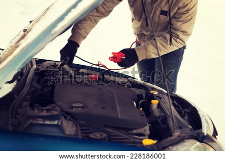 transportation, winter and vehicle concept - closeup of man under bonnet with starter cables - stock photo