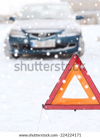 transportation, winter and vehicle concept - closeup of warning triangle and car - stock photo