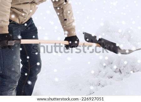 transportation, winter, people and vehicle concept - closeup of man digging snow with shovel - stock photo