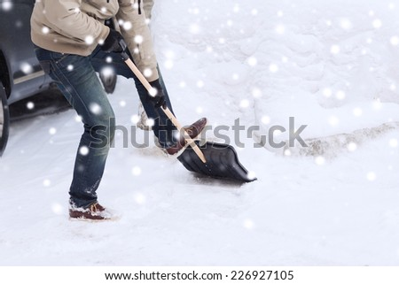 transportation, winter, people and vehicle concept - closeup of man digging snow with shovel near car - stock photo
