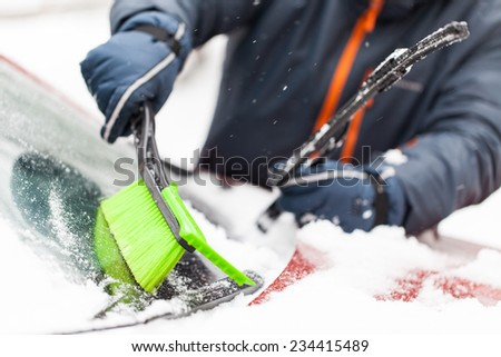 Transportation, winter, weather, people and vehicle concept - man cleaning snow from car with brush - stock photo