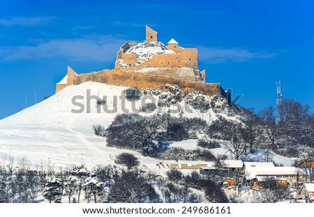 Transylvania, Romania. Winter scenery with ruins of Rupea Fortress, medieval landmark of Hungary Kingdom and Principality of Transylvania. - stock photo