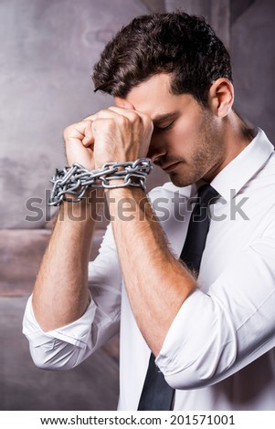 Trapped in chains. Side view of frustrated young man in shirt and tie touching his forehead with hands trapped in chains  - stock photo