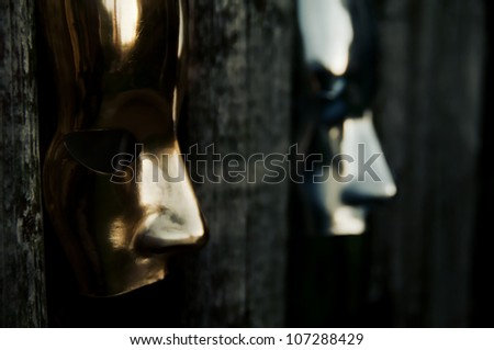 Trapped - Masks behind Weathered Fence - stock photo