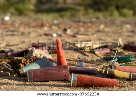 Trash and shotgun shells laying in the dirt