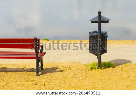 Trash basket with black plastic bag, standing in park in the background of beach. Metal roof of trash. - stock photo