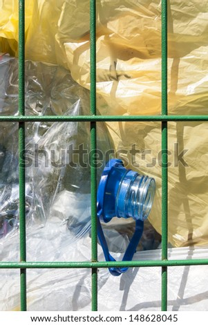 Trash basket with plastic bottles and bags visible. - stock photo