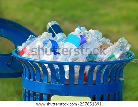 Trash bin full of beverage empty bottles in summer thirsty day - stock photo