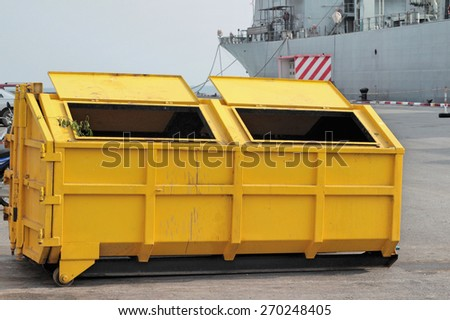 Trash can dustbins big yellow outside. - stock photo