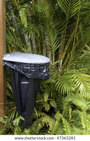 trash can in an exotic forest - stock photo