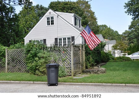 Trash Can Suburban Neighborhood Cape Cod Style Home with American Flag - stock photo