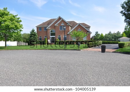 Trash Day Large Brick Suburban Home McMansion Style Architecture Morning Scene - stock photo