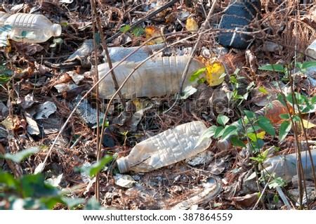 Trash, including plastic water bottles, left on the ground in a park - stock photo
