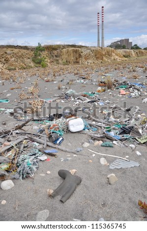 Trash on the seashore next to a factory - stock photo