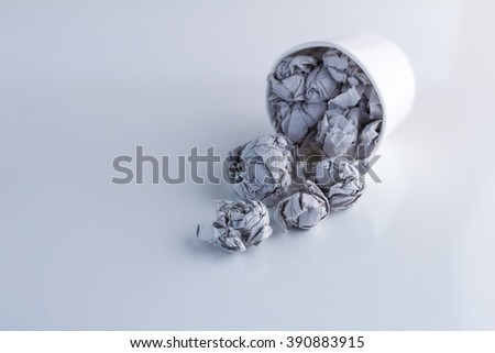 trash paper ball fall from paper cup on white background - stock photo