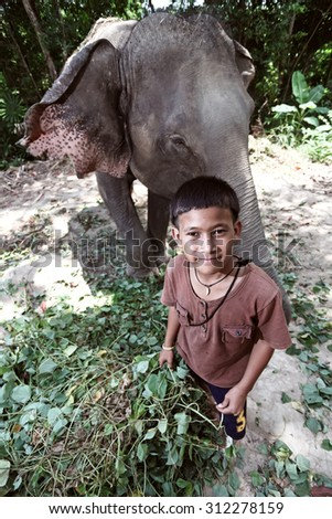 TRAT, THAILAND - APR 15 : Unidentified young man mahout standing next to an elephant eating grass of Koh Mak on April 15, 2011 in Trat, It is a sequence of three of the island in Trat