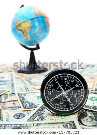 Travel. A compass and the globe on money. - stock photo
