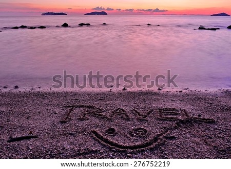Travel. A simple concept image written in the sand beach during sunset - stock photo