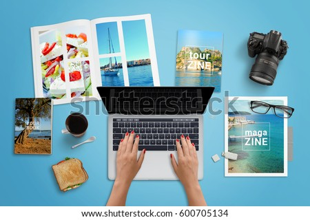 Travel agency work desk. Woman typing on laptop computer with blank screen for mockup. Travel magazines beside. Top view.