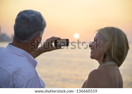 Travel and active elderly man and woman, couple of tourists looking at sea and taking picture with smartphone - stock photo