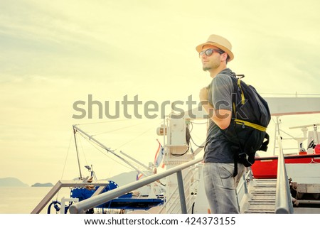 Travel and adventures. Young man with rucksuck on the ship stairs bridge.