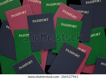 Travel and customs concept of passport books in blue, green, and red - stock photo