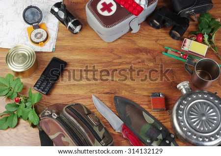 Travel and survival equipment on wooden background - stock photo