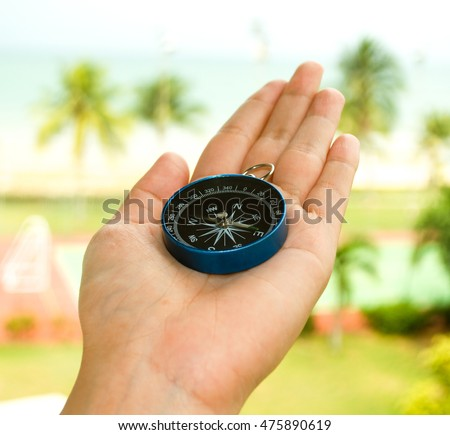 Travel and tourism concept: A compass on a hand find the direction