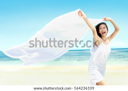 Travel and Vacation. Freedom Concept. Beautiful Girl With White Scarf on The Beach enjoying summer. - stock photo