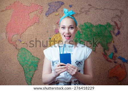Travel around the world. Young happy woman holding passport and tickets while standing against wall with world map. - stock photo