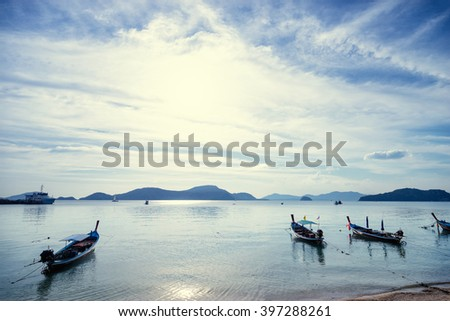 Travel Asia. Beautiful seascape.Traditional Thailand long tail boats with cloudy sky and mountains on horizon. - stock photo
