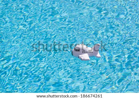 travel background of a toy airplane floating in the rippled blue water of a blue swimming pool  - stock photo