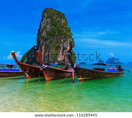 Travel background. Traditional long tail boats in azure sea near Pranang beach, Krabi, Thailand - stock photo
