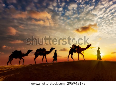 Travel background - two cameleers (camel drivers) with camels silhouettes in dunes of  desert on sunset - stock photo