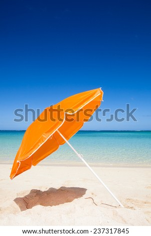 travel background with a beautiful beach with an orange sunshade, turquoise sea, blue sky and white sand, Mauritius, Africa - stock photo