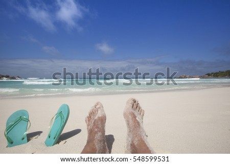 travel background with a pair of turquoise flip-flops and the legs of a caucasian man relaxing at a tropical beach