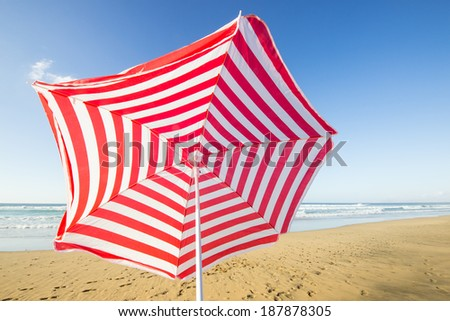 travel background with a red and white sunshade at an endless white beach with a blue sky and a turquoise sea,  Playa de las Pilas, Fuerteventura, canary islands, Spain, Europe