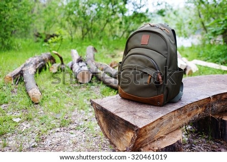Travel backpack on the wooden bench in the forest. Outdoor wanderlust items. Travel, tourism and camping equipment. Picnic rest on the nature. Summer active hiking and trekking tools. - stock photo