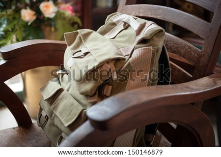 Travel bag on a chair in a restaurant - stock photo