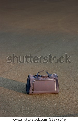 travel bag on asphalt - stock photo