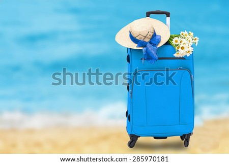 Travel bag with a straw hat and a bouquet of daisies on abstract sea background - stock photo