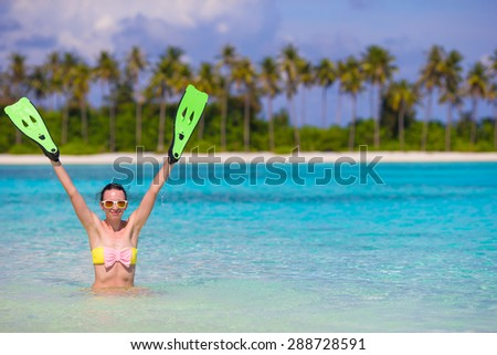 Travel beach fun concept - woman holding snorkeling fins standing in turquiose water - stock photo