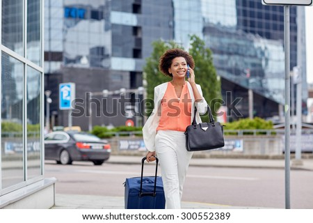 travel, business trip, people and technology concept - happy young african american woman with travel bag walking down city street and calling on smartphone - stock photo