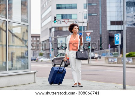 travel, business trip, people and technology concept - happy young african american woman with travel bag and smartphone on city street - stock photo